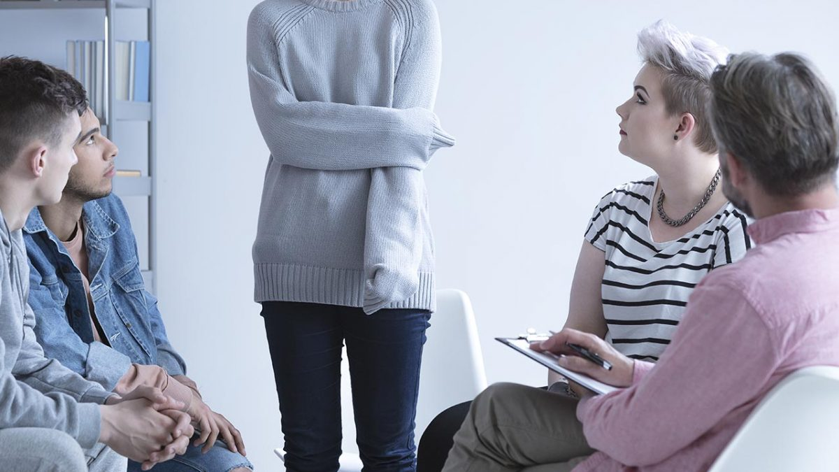Girl with grey sweater standing up talking to four other people