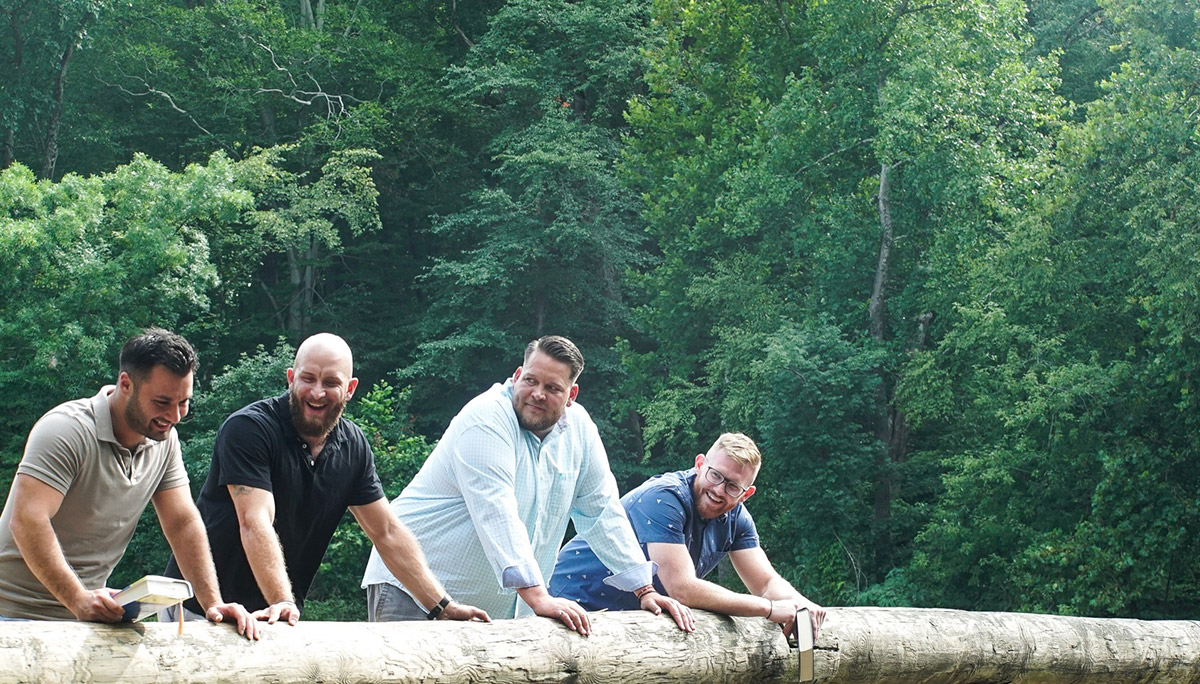 four men laughing on the side of a bridge