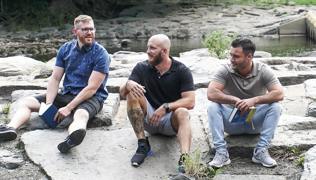 three men sitting on a rock by a river