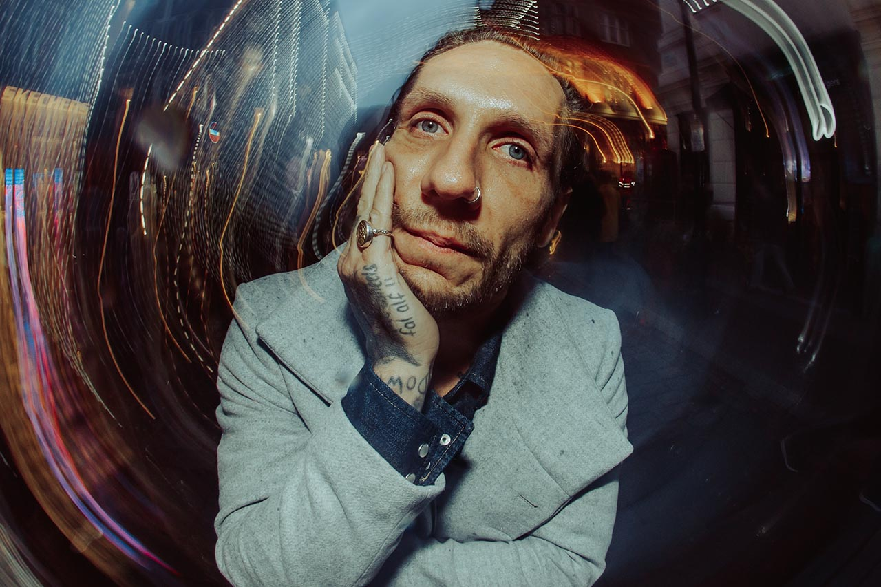 Brandon Novak with a grey coat and a pinky ring